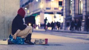 Mann sitzt in einer Einkaufsstraße. Er sitzt auf einer Tüte und vor ihm steht eine beschriftete Pappe. Er muss betteln.